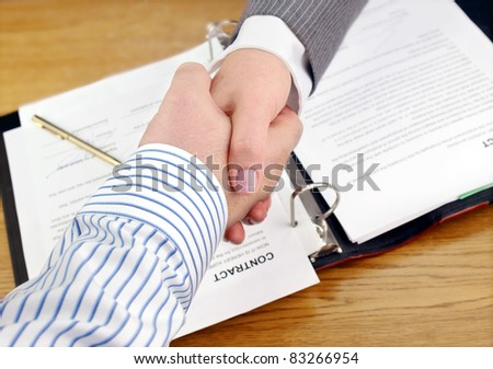 Closeup of businessmen and businesswoman shaking hands over the signed contract.
