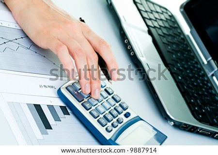 Closeup of businesswoman's fingers touching calculator buttons and holding a pen with a laptop and a diagram near by