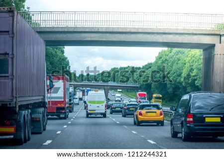Closeup of busy Highway transportation  motorway full of cars in the evening with dark cloudy blue sky, going under bridge