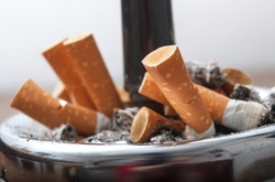 closeup of butts of cigarettes in full ashtray