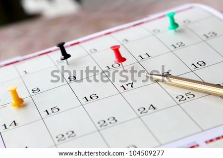 Closeup of calendar page with marked important days and pen