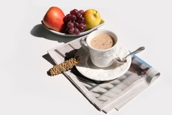 closeup of cappuccino coffee in a white cup and saucer on a white background, cookies, fruit, morning newspaper, hard light, coffee time concept, sunny day, news