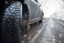 Closeup of car spikes  tires in winter on the road covered with snow. ice on the road