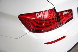 Closeup of car tail light on a white car.