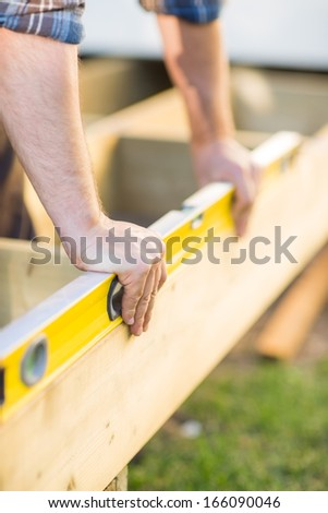 Closeup of carpenter\'s hands checking level of wood at construction site