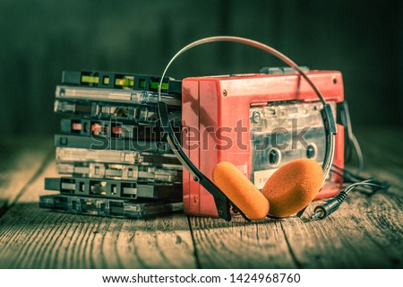 Photo of  Closeup of cassette tape, red walkman and headphones