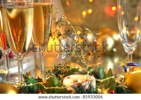 Closeup of champagne in glasses,baubles,candle lights on golden background with twinkle lights.
