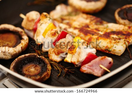Closeup of champignon mushrooms, spiced ham, pork meat and vegetables spit in the frying pan on the stove, selective focus - stock photo