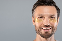 Closeup of cheerful middle-aged bearded man with eye patches, copy space. Happy man having face care procedures, grey studio background. Anti-aging, lifting, anti-wrinkles procedures for men