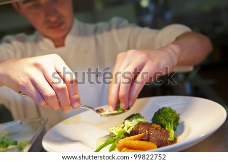 Closeup of chef adding finishing touch on his dish before it goes on the table.