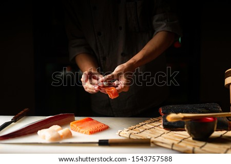 Closeup of chef hands preparing japanese food. Japanese chef making sushi at restaurant. Young chef making traditional japanese sushi on cuting board .