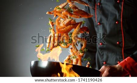 Closeup of chef throwing prawns from wok pan in fire. Fresh asian food preparation on dark background. Zdjęcia stock ©