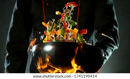 Closeup of chef throwing vegetable mix from wok pan in fire. Fresh asian food preparation on dark background. Zdjęcia stock ©