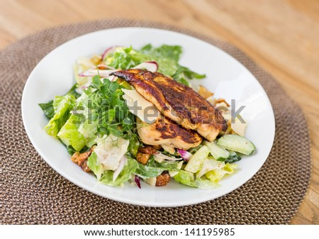 Closeup of chicken caesar salad with vegetables on plate