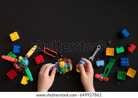 Closeup of child's hands with colorful plastic bricks and details of toys on black paper background. Boy or girl playing with parts of bright small spare parts for toys on black table surface