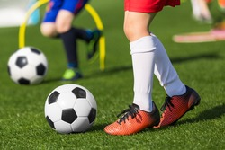Closeup of child soccer player legs kicking ball. Kid running classic black and white football ball. School children on soccer playfield. Kids practicing sports on grass pitch