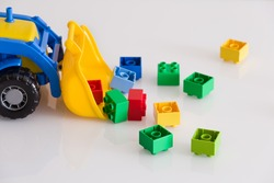 Closeup of children toy tractor with colorful plastic bricks or details on white background. Baby's toys on the table isolated.