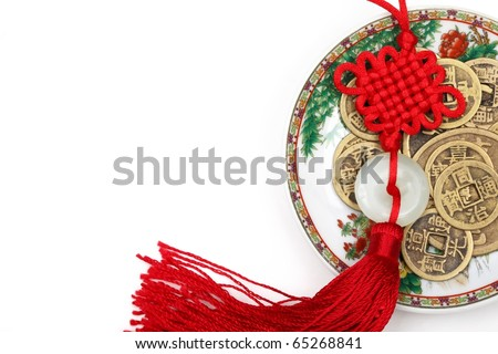 Closeup of Chinese lucky knot and ancient copper coin in plate. - stock photo