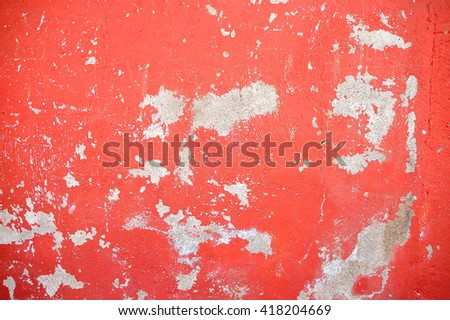 closeup of chipped paint on red wall