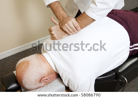 Closeup of chiropractors hands doing spinal adjustment on senior man.