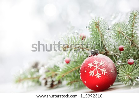 Closeup of Christmas ball with pine branch on abstract background.