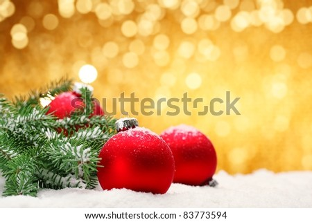 Closeup of Christmas balls with pine branch on festive background.