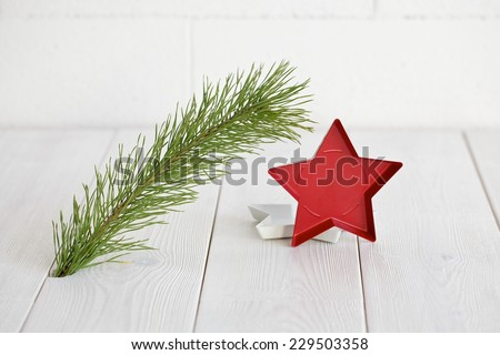 Closeup of Christmas interior decoration in simple, minimalist, elegant style with pine branch on white wood floor and wall background. Plenty of copy space.