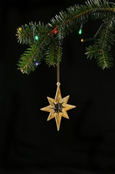 Closeup of Christmas tree with lights and hanging gold glitter star against a black background