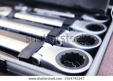Closeup of chrome wrench tools organized in box.  Set of tool equipment. Many wrenches in different sizes.  #1564743247