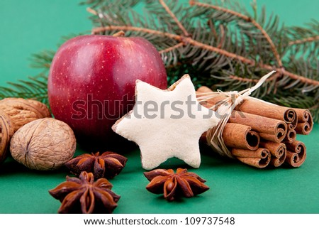 closeup of cinnamon, anise, walnut and christmas decoration on green background isolated