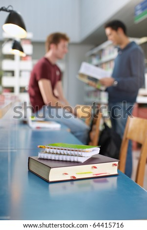 closeup of closed book on table. Two students talking in background. Vertical shape, copy space, focus on foreground