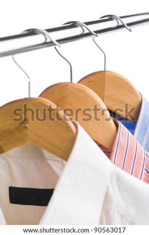 closeup of clothes hanger with shirts on white