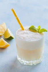 Closeup of coconut, lemon and lime lemonade. Glass with white opaque drink, pieces of fresh lemons and limes, mint, ice. Copy space.