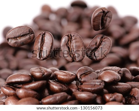 Closeup of coffee beans floating above large group