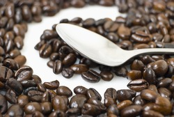 Closeup of coffee beans framing letter C; teaspoon on coffee beans