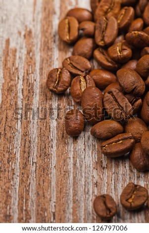 closeup of coffee beans over wooden background
