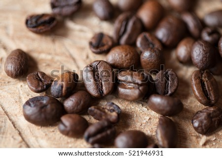 Closeup of coffee beans with focus on one, on rustic wooden background  #521946931
