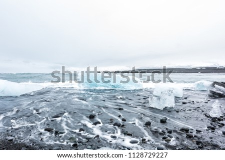 Stock Photo Closeup of cold winter one blue glacier iceberg in Jokulsaron lagoon lake diamond beach in Iceland, black sand and long exposure smooth waves shore