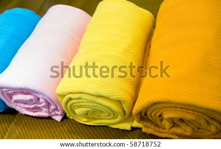 Closeup of colorful bath towels, rolled and piled.