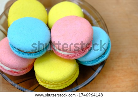 Closeup of Colorful french Sweet Pastries Macaroons on glass plate on a wooden tray isolated on white background.