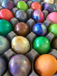 Closeup of colorful painted Easter eggs in a carton. The eggs are metallic gold, purple, green, brown, and tie dyed. Painted by kids.