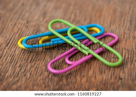 closeup of colorful paperclips on wooden desk background