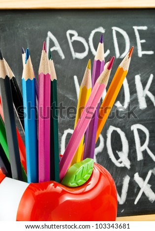 Closeup of colorful pencils against school blackboard.