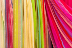 Closeup of colorful scarves hanging in the market.  Shallow deep of focus.