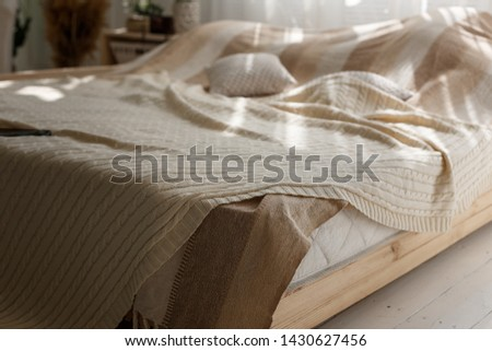 Closeup of comfort double bed with beige pillows and a blanket, sun beams and shadows in cozy bedroom.