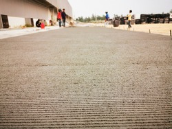 Closeup of concrete on a driveway, worker is waiting harden concrete, Photo is blur style use for backgound.