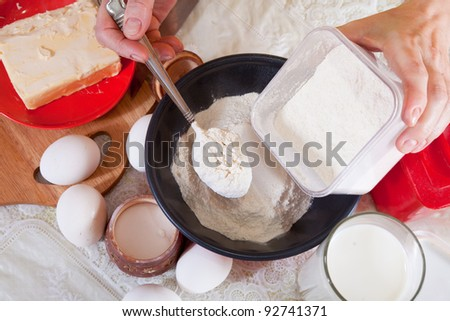 Closeup of cook hands pours  flour in to pan