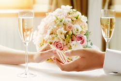 Closeup of couple hands on restaurant table with bouquet and glases of shampagne. Romantic couple holding each other's hand at dinner in a luxury restaurant. Marriage proposal and engagement concept.