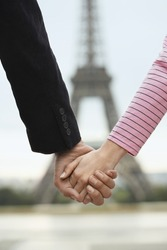 Closeup of couple holding hands in front of blurred Eiffel Tower