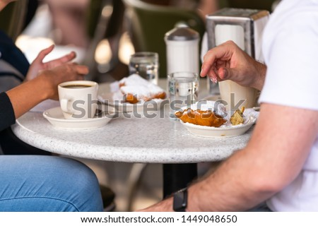 Closeup of couple sitting outside at sidewalk cafe by table drinking chicory coffee and eating deep fried beignet donut powdered with sugar Stock fotó ©
